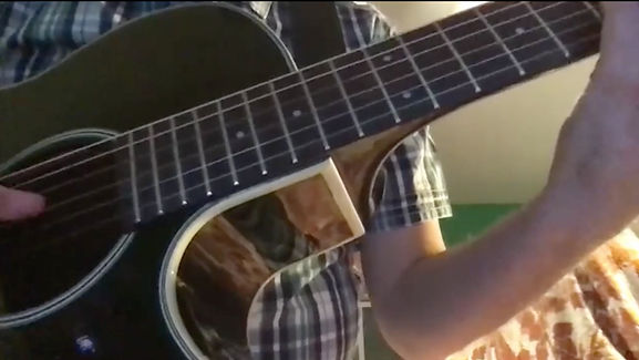 En gitarr i närbild. Någons händer är i position för att spela.