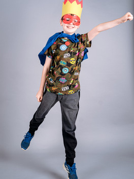 A smiling boy standing in superhero pose wears a yellow and red crown, blue superhero cape and brown t-shirt with superhero logos on it
