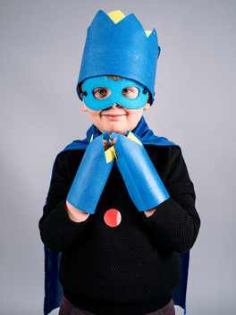 A close up of a smiling young boy hands brought together under his chin, he wears a blue cape, crown, cuffs and eye mask