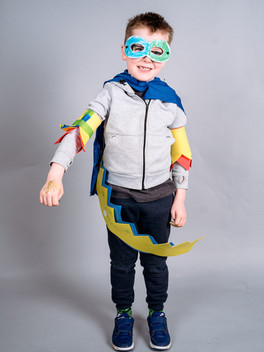 a young boy in superhero pose with a green and blue coloured-in mask, yellow and red arm cuffs and a colourful belt.