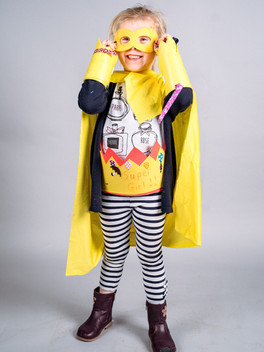 A young girl dresses in bright yellow superhero outfit smiles and laughs