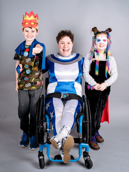 Touretteshero in her superhero costume sitting in her wheelchair smiles, with a young boy and girl either side of her also smiling in their superhero costumes