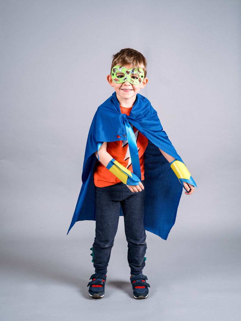 a young boy in blue cape, green mask and bright red thunder bolt t-shirt smiles