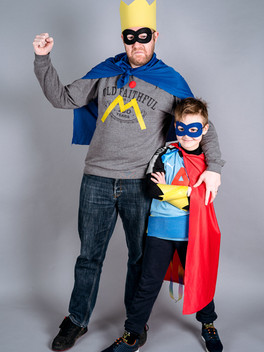 A dad and son superhero due stand together side on in superhero poses, smiling.