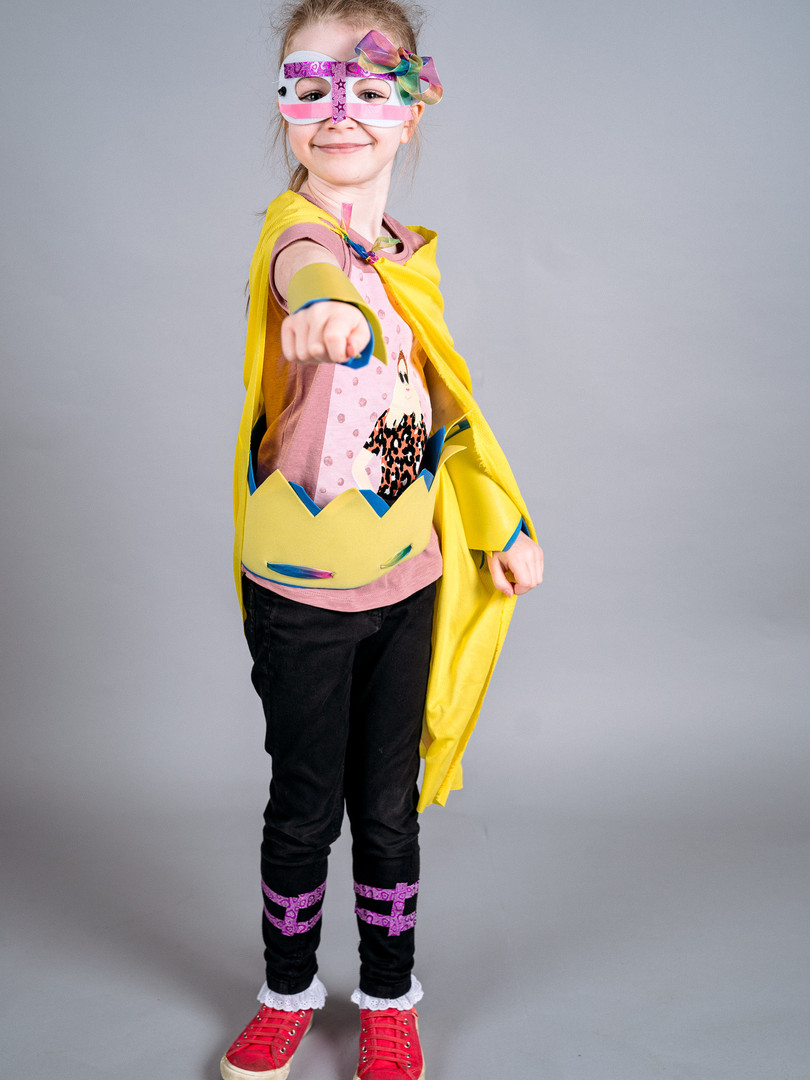 A young girl stands smiling in superhero pose wearing a yellow cape, a pink mask with a bow and red sparkly trainers