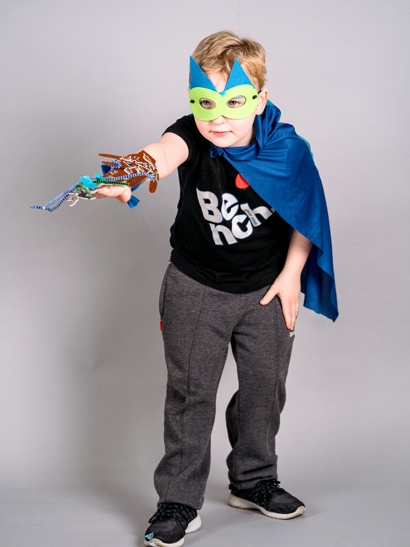 a young boy in black top and green masks leans over as it about to fly, on his arm is a thunderboltcuff