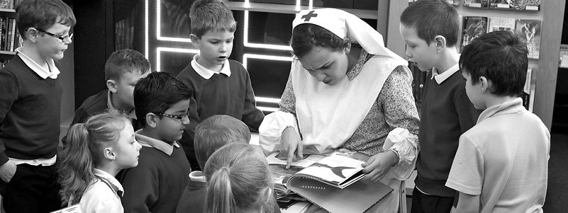 A black and white image of a lady dressed as an old fashioned nurse reading a book surrounded by excited children
