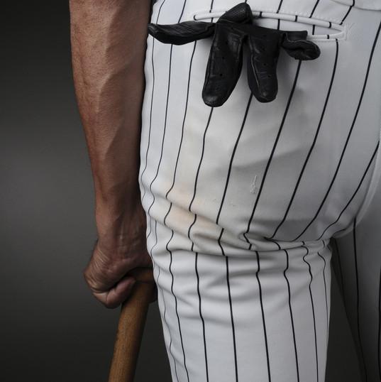close-up-baseball-player-leaning-on-bat.