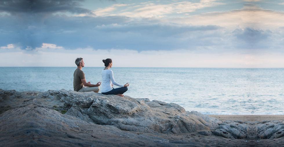 Couple meditate beach AdobeStock_1698634