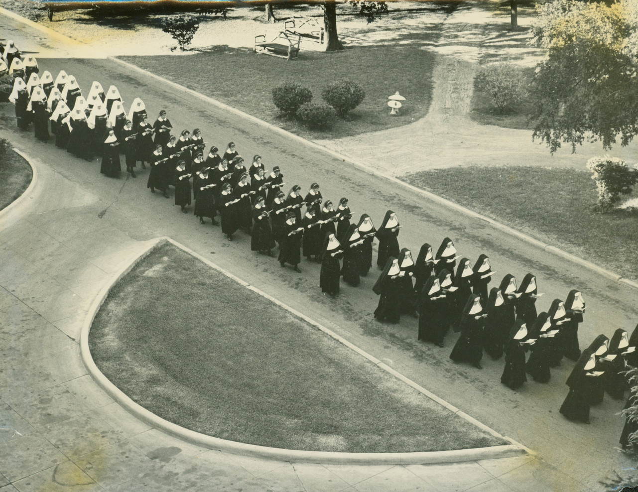 Procession of Postulants, Novices, and Sisters between the Motherhouse and Incarnate Word College.