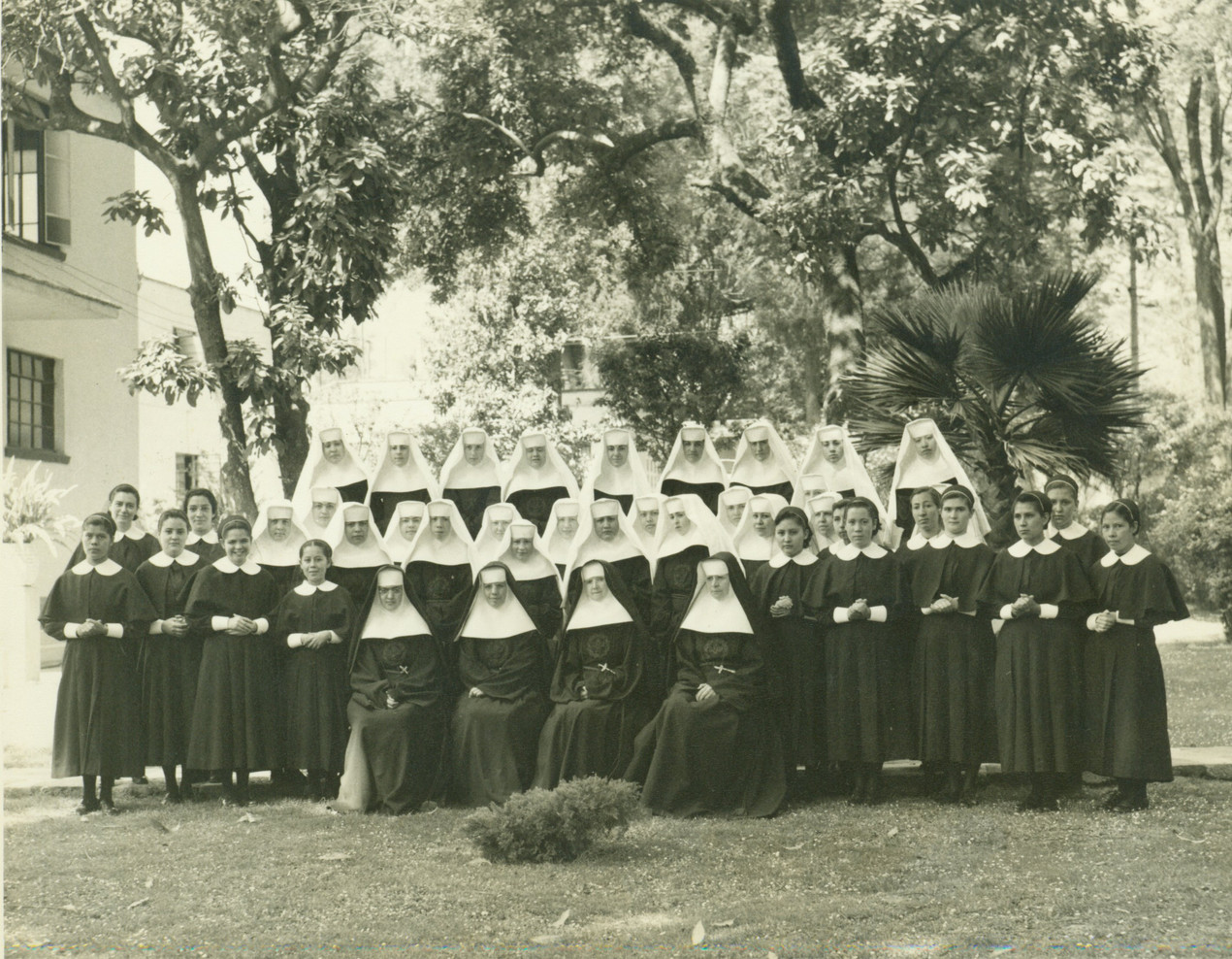 Until the mid-20th century, Catholic Sisters wore distinctive clothing. This photograph from the congregation shows women wearing black veils, who are professed sisters. Novices, who are not fully invested, wear white veils. Young women in collared dresses are postulants still receiving instruction.
