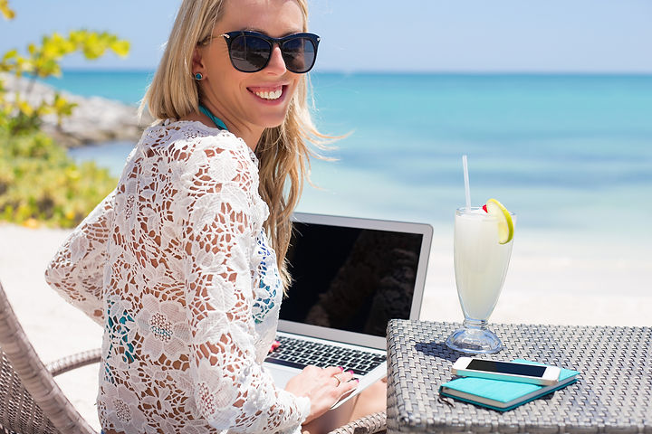 Successful business woman working with computer on the beach.jpg