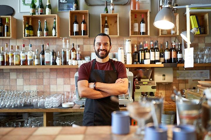 small business, people and service concept - happy man or waiter in apron at bar or coffee shop.jpg