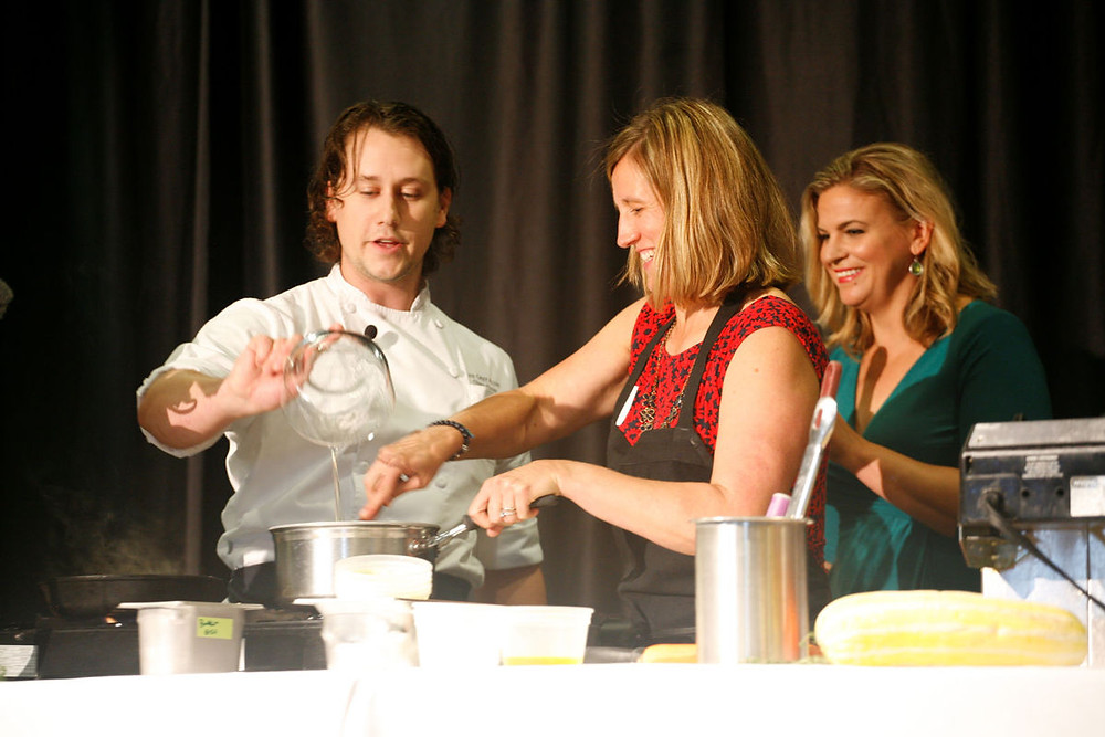 Chef Chase Grove of The Grey Plume makes ice cream with the help of guest sous chef Jen Parker. Behind is master of ceremonies Kayla Thomas.