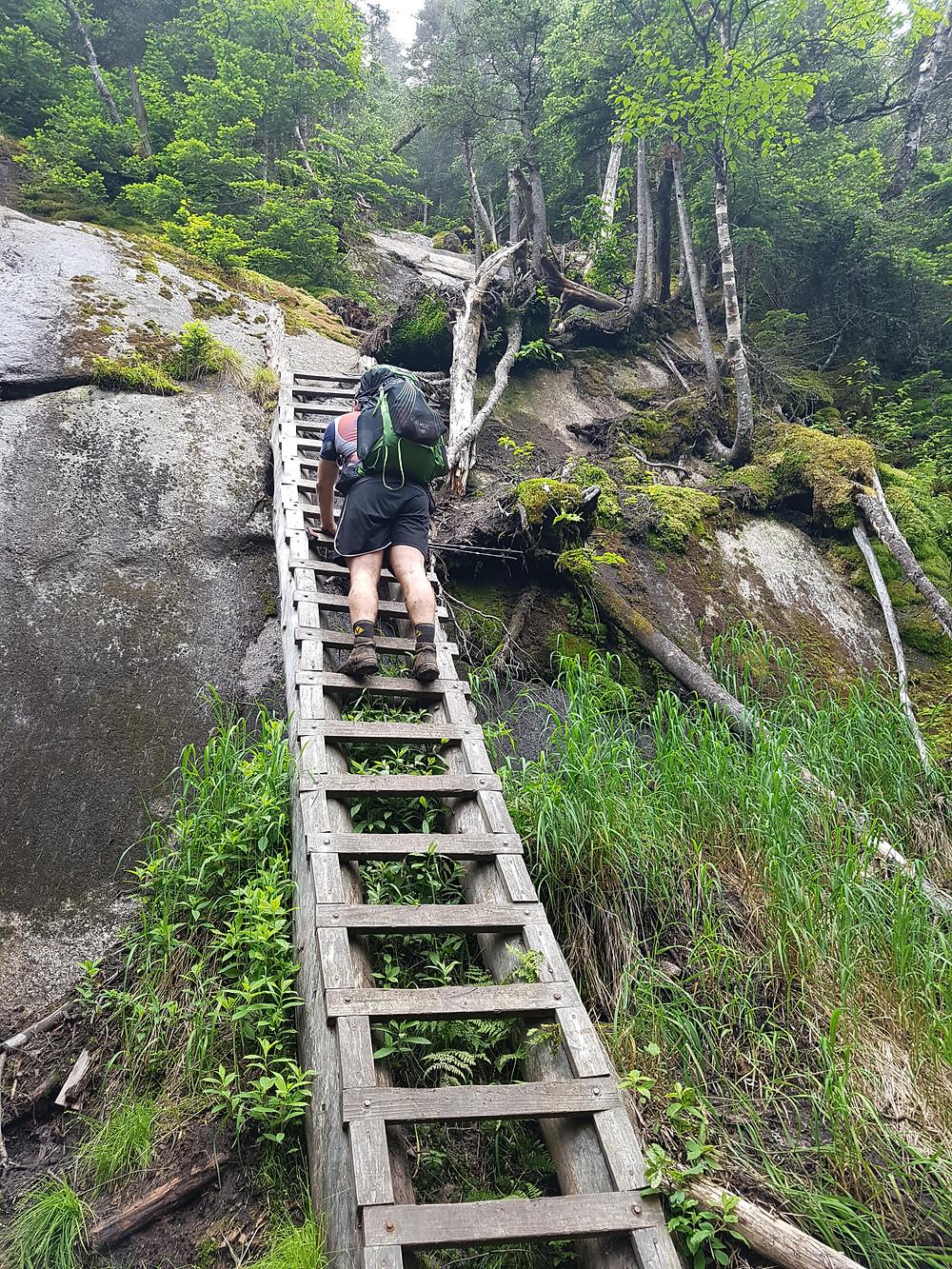 Climbing a wooden ladder up a cliff