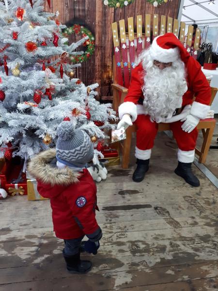 """""""Il eut la chance de faire la connaissance quelques jours plus tard du vrai papa Noël (tout du moins, celui qu'incarnait mon oncle). Avait-il apprécié cette rencontre, ou était-ce plus pour nous, pour avoir de belles photos ? L'histoire ne le dit pas... Mais oui, il était sans doute bien trop jeune pour bien comprendre qui était ce gros bonhomme rouge avec une énorme barbe blanche. """"  Notez que la ressemblance avec le vrai père Noël, est quand même frappante."""