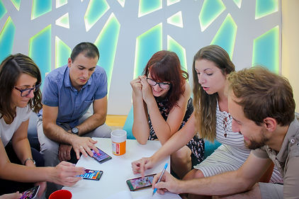 A team of game developers is brainstorming with the help of their cell phones.