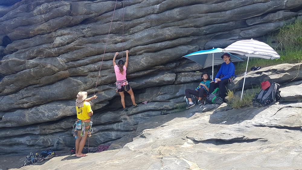 """Patricia Manzi escaladando a """"Pedra Voadora"""" enquanto João Pedro e Laura aproveitam a estrutura """"social"""" montada na base"""