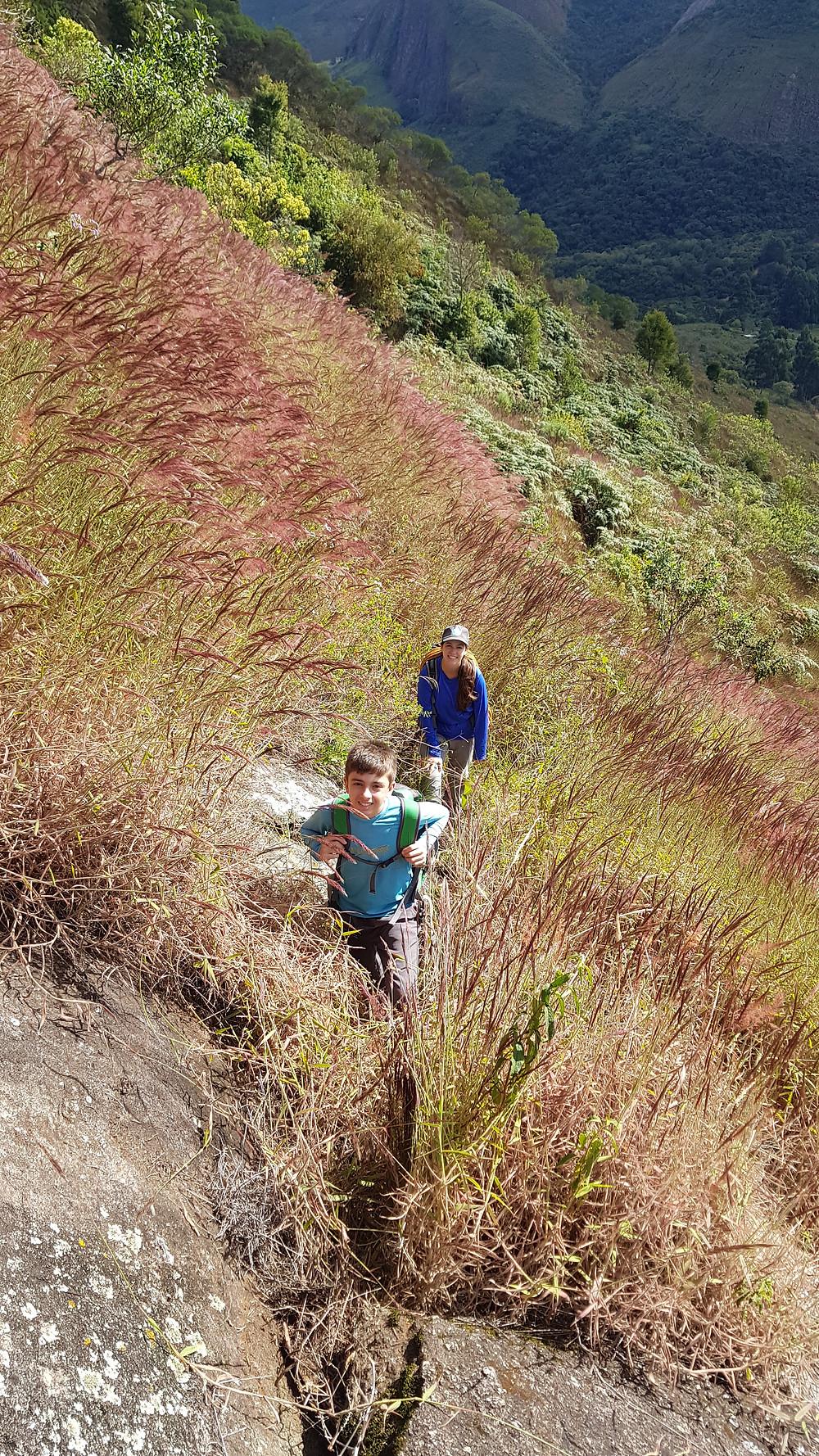 """João Pedro e Laura Petroni na trilha, próximos à base da """"Porta de Entrada"""" (2° IIIsup E3 D1 - 150m)"""