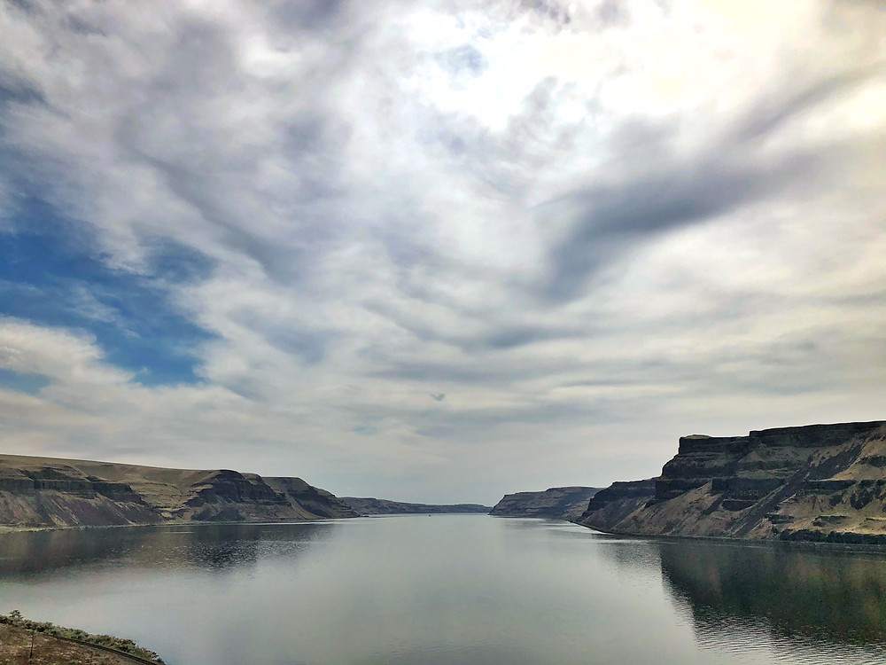 Landscape image of a river bed with dramatic skies and calm waters