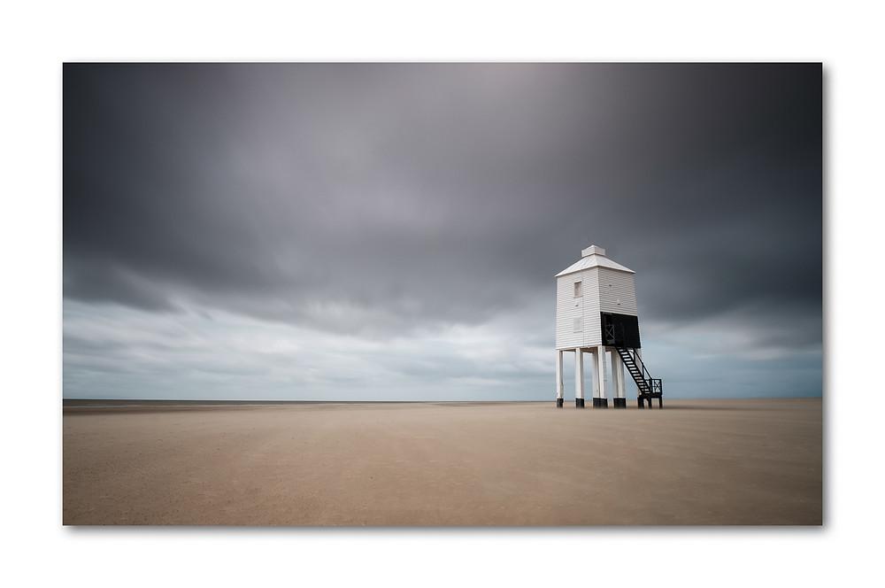 Lighthouse on desolate beach under a foreboding sky