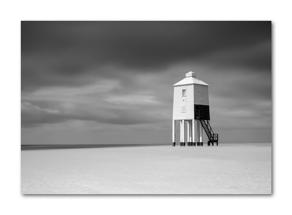 Lighthouse with dark sky and blowing sand
