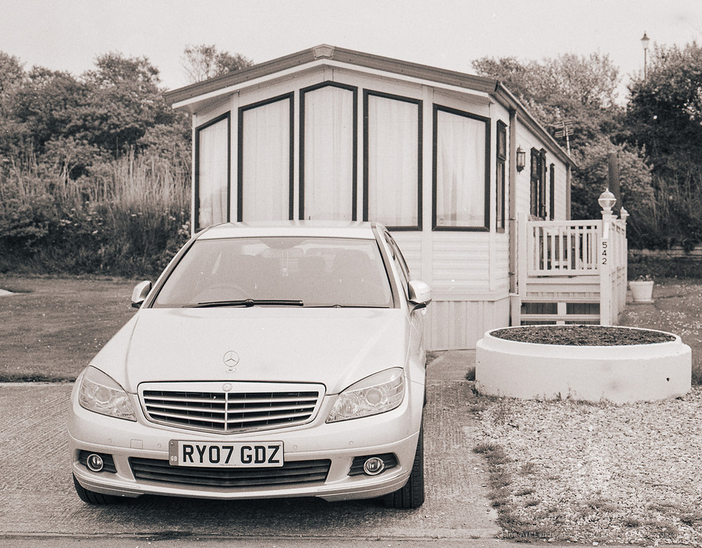 This image of a Merceds Benz car parked outside a spanking new Chalet challenges the perception of the English Seaside as cheap and Cheerful, a place for Kiss-me-quick hats and lager by the bucket load. This may indicate a change to Chardonnay and sensible footwear.