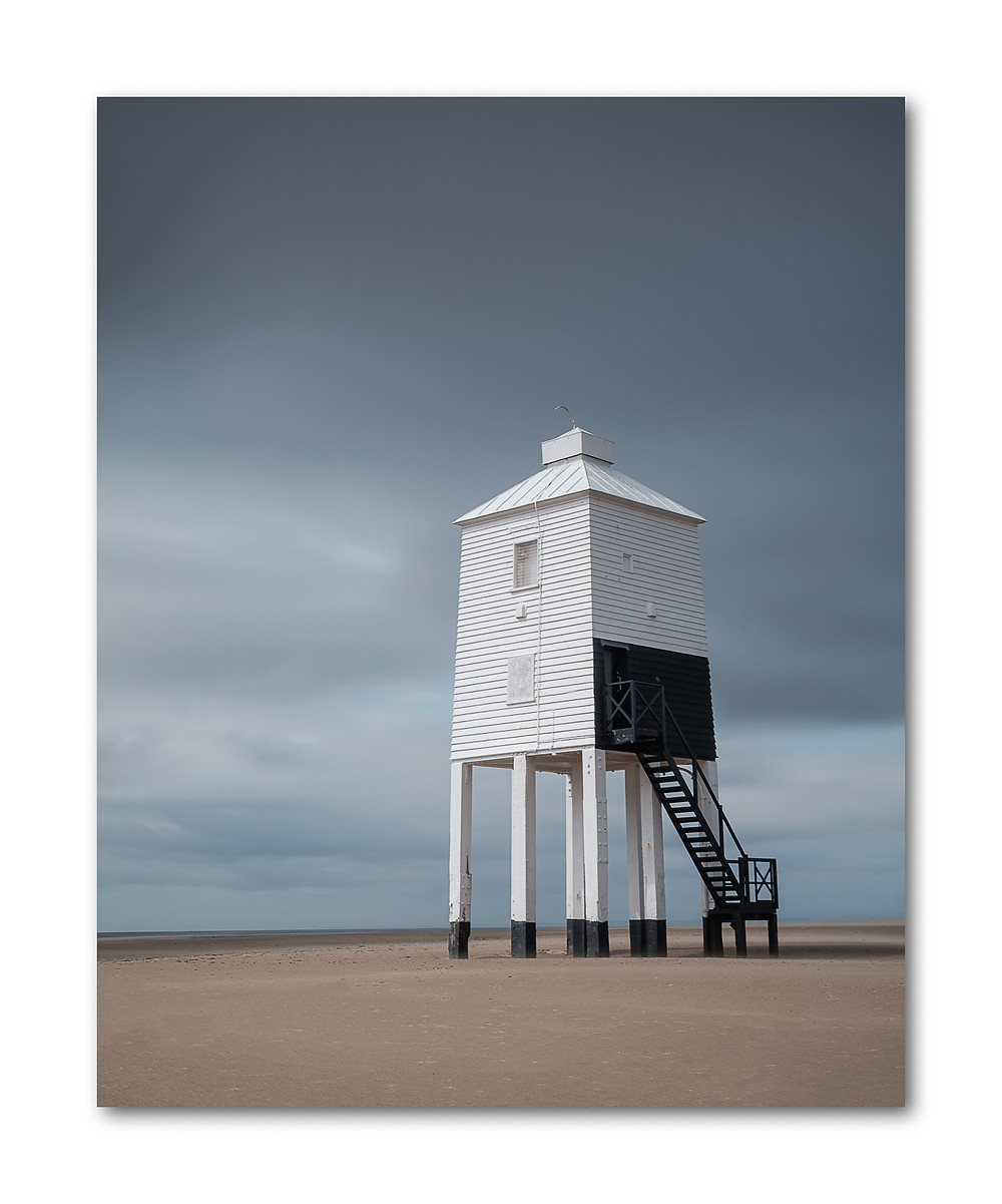 Portrait colour image of a Wooden Lighthouse under a stormy sky
