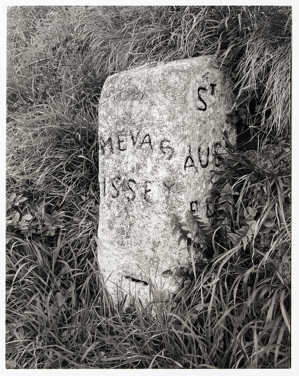 weathered  granite milestone, whitewashed with crudely painted letters