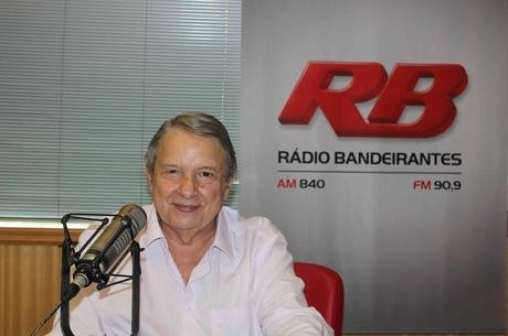 Jornalista e radialista José Paulo de Andrade sentado com um sorriso nos lábios e um microfone a sua frente, com o logo da Rádio Bandeirantes ao fundo.