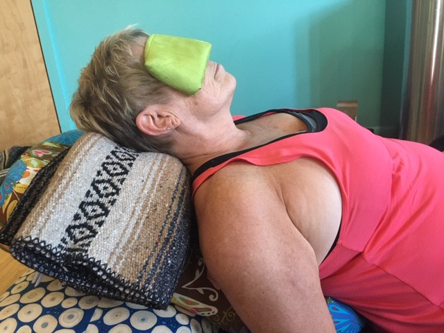 Woman relaxing on bolsters and blankets during yoga class. She has a green eye pillow over her eyes and a serene expression on her face.