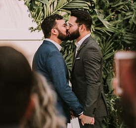 men-wearing-suit-kissing-in-front-of-peo
