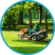 a person on a riding lawn mower cutting a field of grass