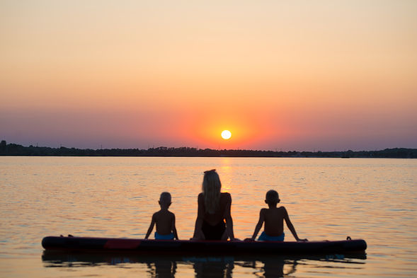 Mother and two children sit on on paddle board and look at the sunset.Water sports , activ...e._.jpg
