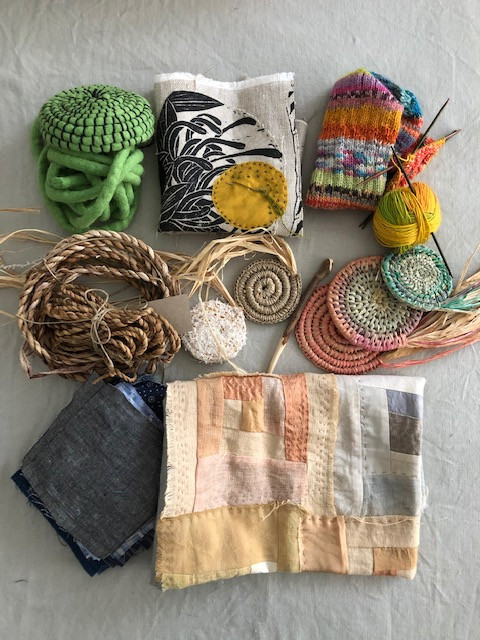 This is a picture of unfinished craft projects. There's some stitchwork, raffia and textile baskets all in different colours