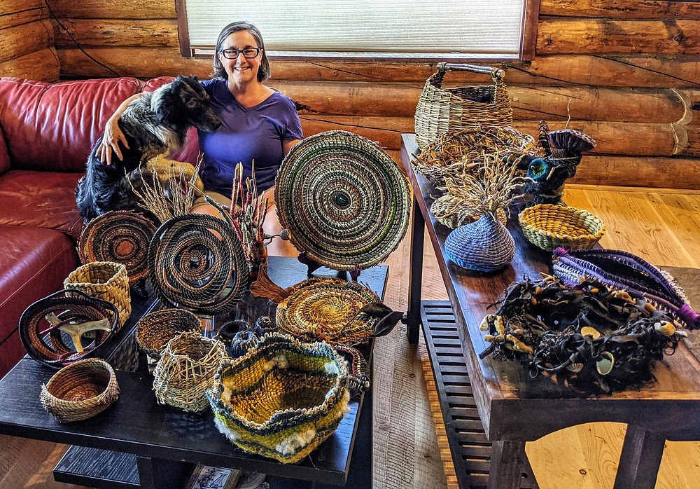 This is a picture of Lisa with her dog, Tazzie. They are sitting on a red couch behind a bunch of hand made baskets in natural blueish tones.