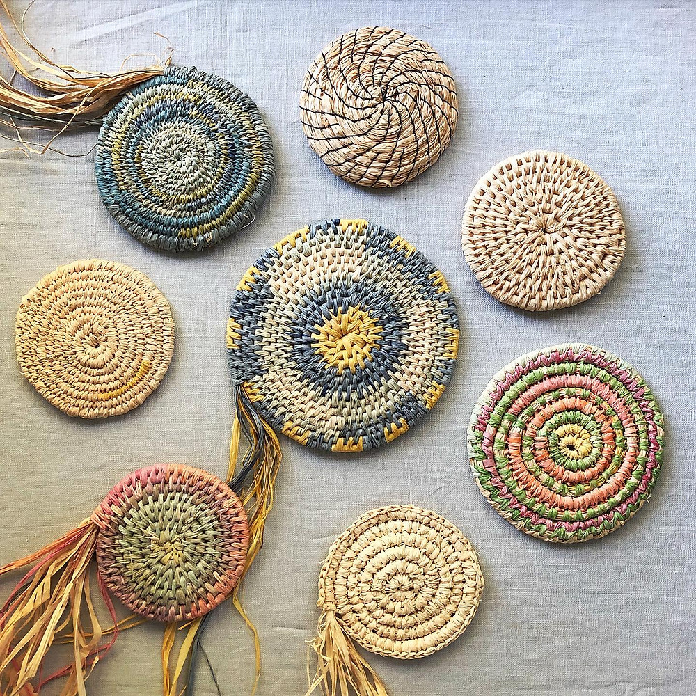 This is a flat lay of raffia baskets that have just been started, There are plain coloured and pink and blue baskets.