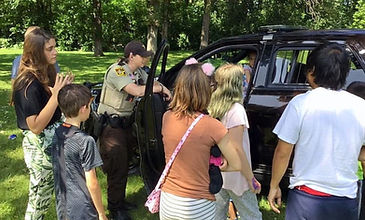Children gathered around police officer at Annual Community Cookout
