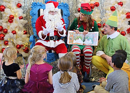 Santa sits in chair and signs a story to children sitting at his feet