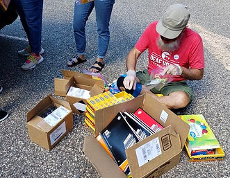 Deaf Equity Volunteer sitting on ground collecting school supplies