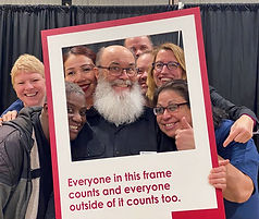 """Diverse group of people smiling and laughing while holding an over sized frame that says """"Everyone in this frame counts and everyone outaside it counts too."""""""