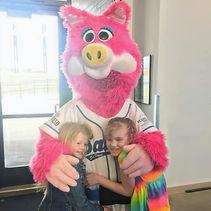 Two children hug bright pink, furry sports mascot