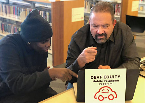 Two Deaf Equity Volunteers sit at computer discussing the Mobile Volunteer Program