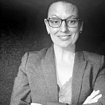woman smiling in glasses with blazer on