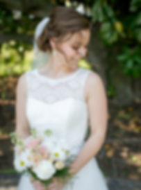 Our bride, Jessica, smiles softly in front of a manolia tree in Williamsburg.