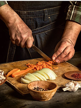 man-cuts-carrots-near-raw-vegetables-bro