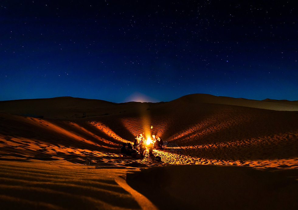 people-having-bonfire-at-desert-at-night