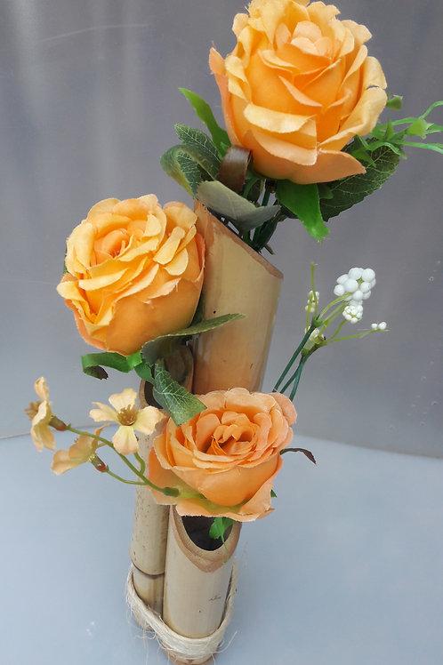 Arranjo de bambu com rosas laranjas.