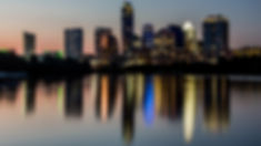 Snapshot of the Austin skyline- it is dusk, and there are lights of various colors reflecting off the Colorado river.
