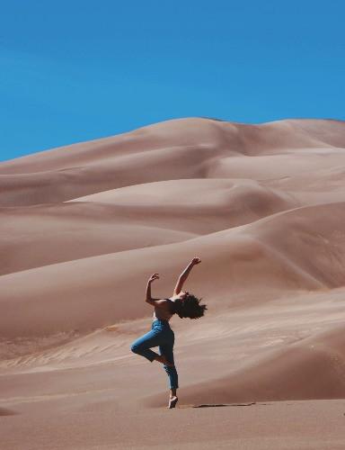 Frau tanzt in der Wueste